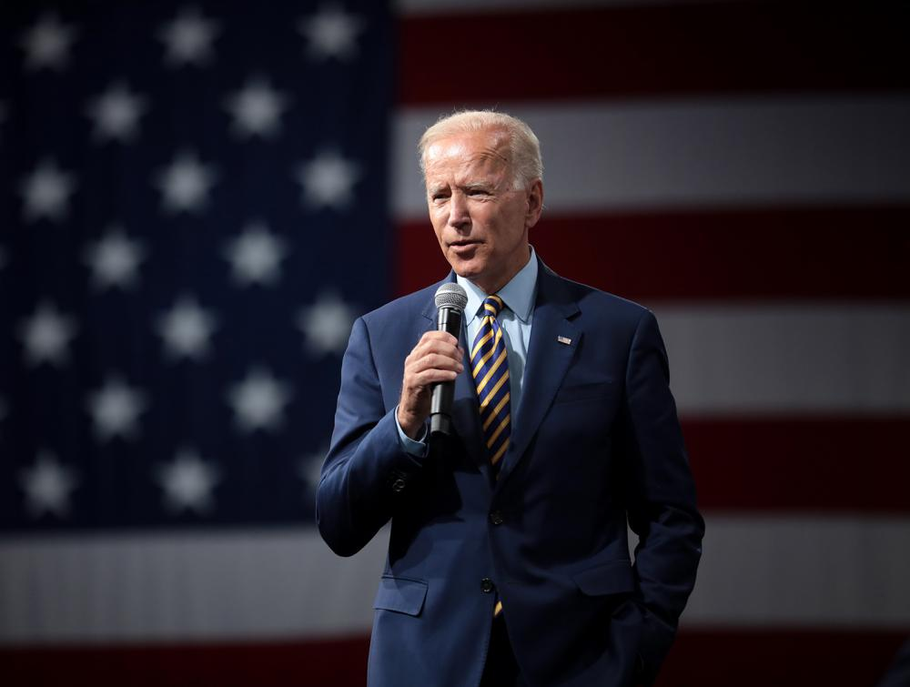 Joe Biden standing in front of an American flag, holding a microphone