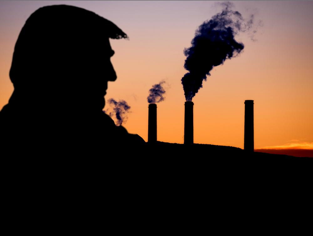 Black silhouette against sunset sky of man on left side of screen facing several belching smokestacks